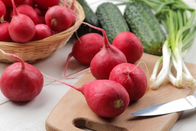 Rabanete fresco. rabanetes de legumes frescos de primavera, pepino, cebolinha e verdes em uma mesa de madeira branca. ingredientes para cozinhar.