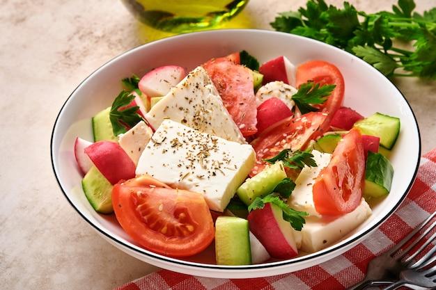 Rabanete, pepino, tomate, pimenta e queijo feta com especiarias pimenta e azeite em uma tigela branca em ardósia cinza, pedra ou fundo de concreto. conceito de comida saudável. vista do topo.