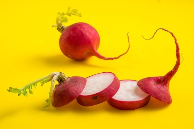 Rabanete vermelho fatiado maduro na superfície amarela