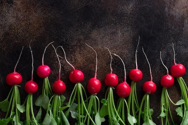 Rabanete vermelho maduro com tops verdes em uma mesa de concreto escura