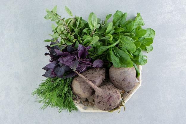 Rabanetes deliciosos com verduras na tigela, no fundo de mármore.