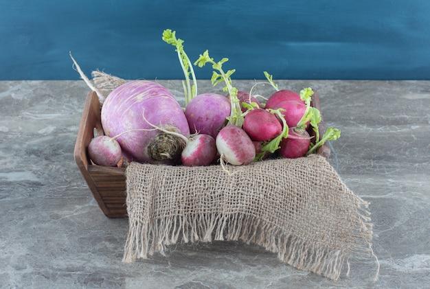 Rabanetes deliciosos em toalha na caixa, na mesa de mármore.