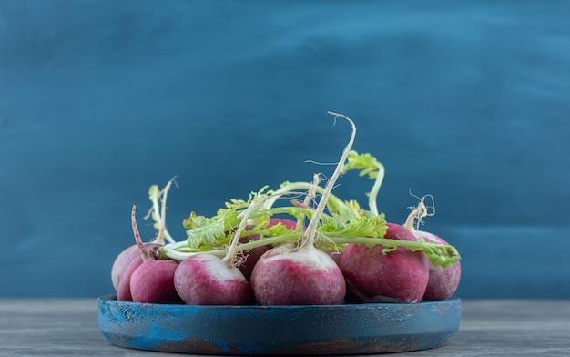 Rabanetes deliciosos na tigela, na mesa de mármore.