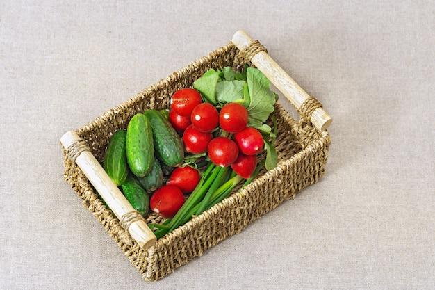 Rabanetes frescos, pepinos, cebolas verdes na caixa. cesta de legumes.