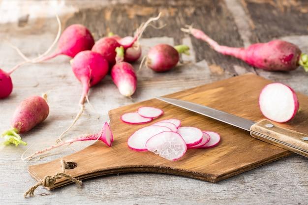 Rabanetes frescos picados e uma faca em uma placa de corte em uma mesa de madeira. estilo rústico.