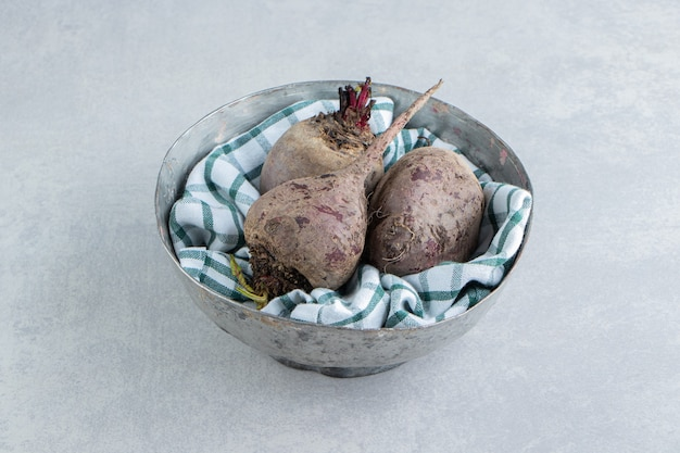 Rabanetes maduros na toalha, na tigela, no fundo de mármore.
