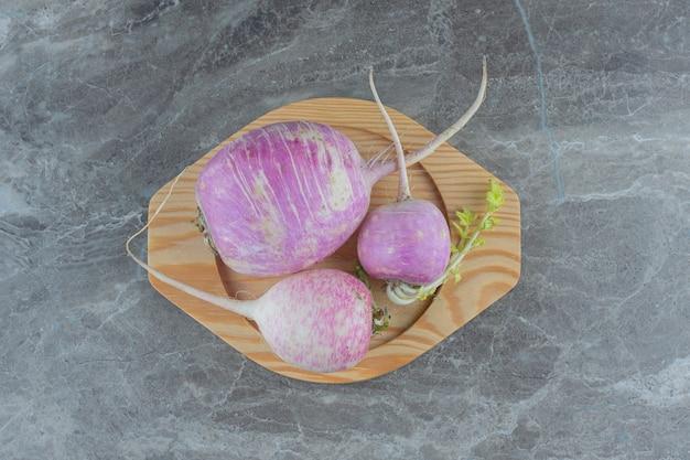 Rabanetes saborosos na placa de madeira, na mesa de mármore.