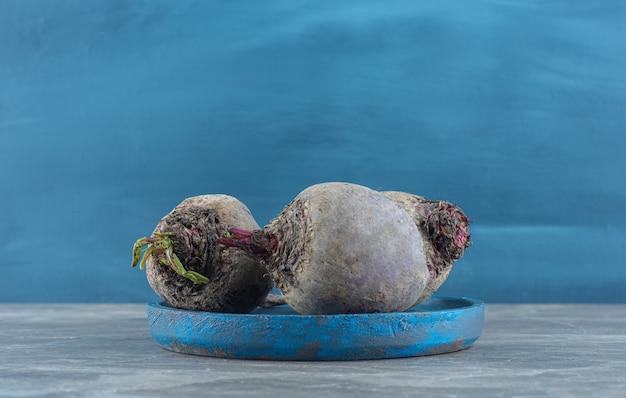 Rabanetes saborosos na tigela, na mesa de mármore.