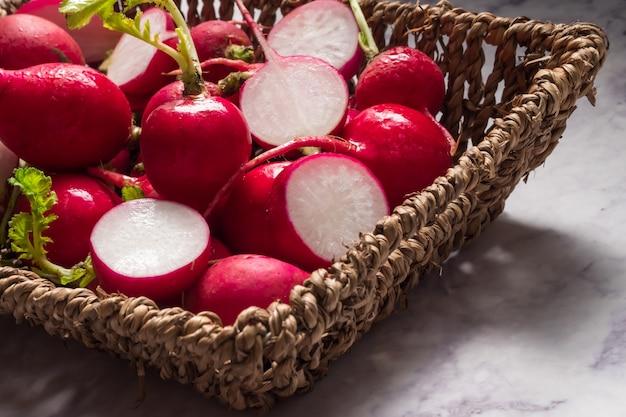 Rabanetes vermelhos fatiados em uma cesta com grunge