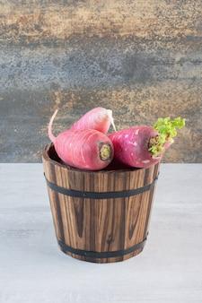 Rabanetes vermelhos frescos em balde de madeira. foto de alta qualidade