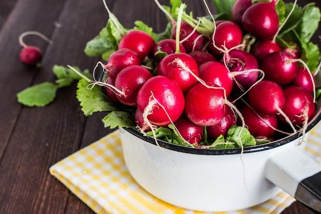 Rabanetes vermelhos na tigela na mesa de madeira