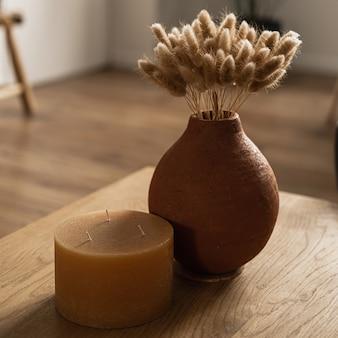 Rabo coelho buquê de grama em uma panela de barro, vela na mesa de madeira maciça