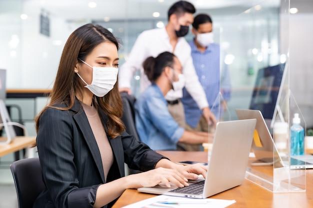 Raça mista de empresários africanos e asiáticos usando máscaras no escritório