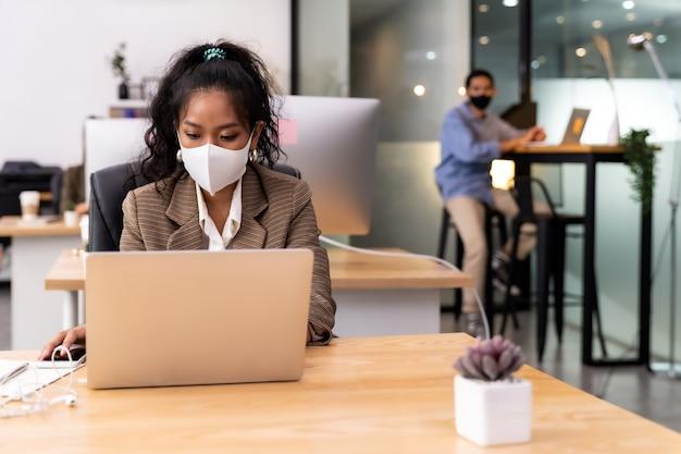 Raça mista de mulher de negócios africana negra e asiática usa máscara facial, trabalhando em um novo escritório normal.