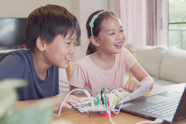 Raça mista jovens crianças asiáticas se divertindo aprendendo a codificar juntos, aprendendo remotamente em casa, ciência stem, educação em casa, distanciamento social, conceito de isolamento