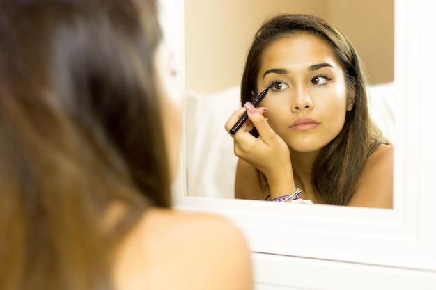 Raça mista, mulher jovem, com, escova, olho forro, ligado, olhando espelho