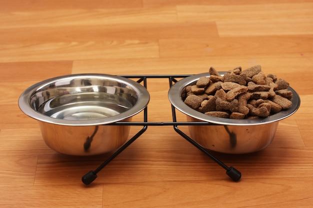 Ração de cachorro seca e água em tigelas de metal no chão