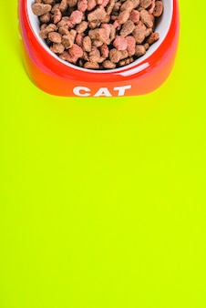 Ração de gato seco em uma tigela vermelha com espaço de cópia