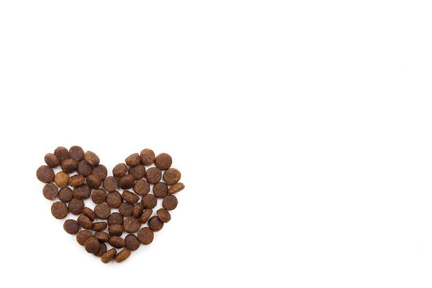 Ração seca para cães e gatos em forma de coração isolado no fundo branco, cópia espaço, vista superior. comida para animais de estimação em forma de coração. alimentos para cães e gatos. conceito de comida saudável para animais de estimação.