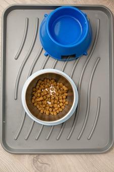 Ração seca para cães e tigelas de água dentro de casa