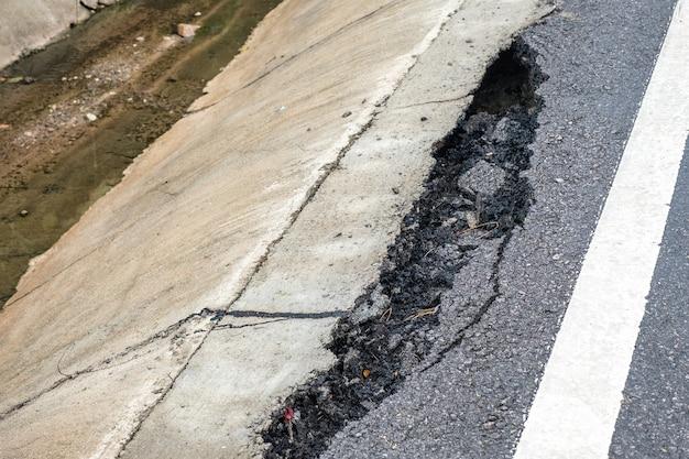 Rachada e quebrada da superfície da estrada de asfalto na beira da estrada