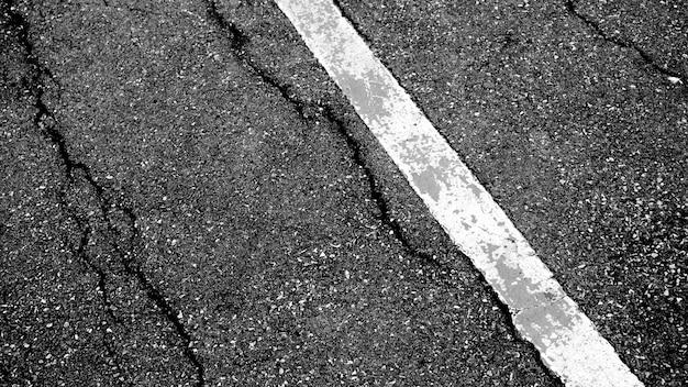 Rachadura e textura da estrada asfaltada com linha tracejada branca fundo da opinião superior.