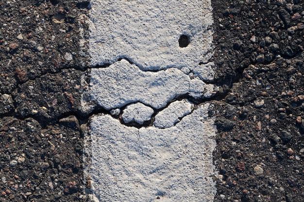 Rachadura em uma estrada de asfalto, com uma linha de marcação rodoviária pintada de branco para carros