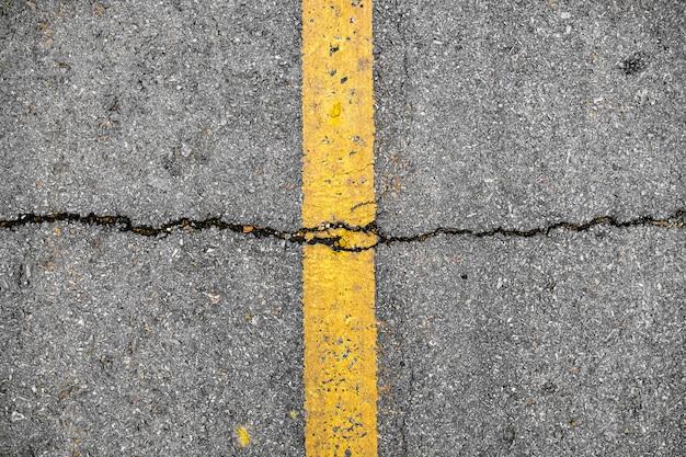 Rachadura na linha amarela na textura da estrada