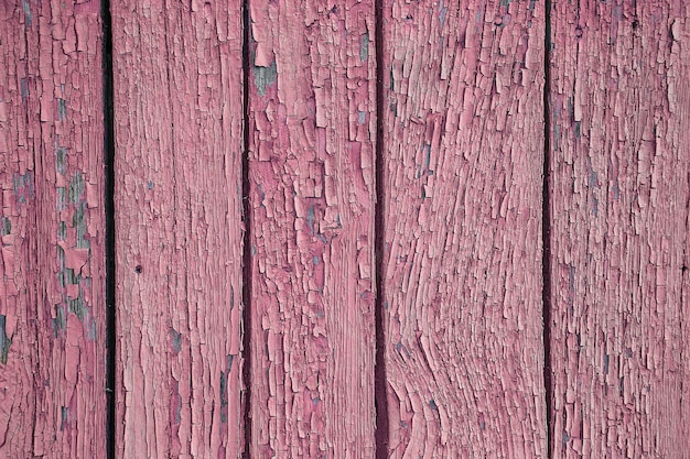 Rachaduras e descascando tinta rosa em uma parede. fundo de madeira vintage com pintura descascada verde. quadro antigo com tinta irradiada