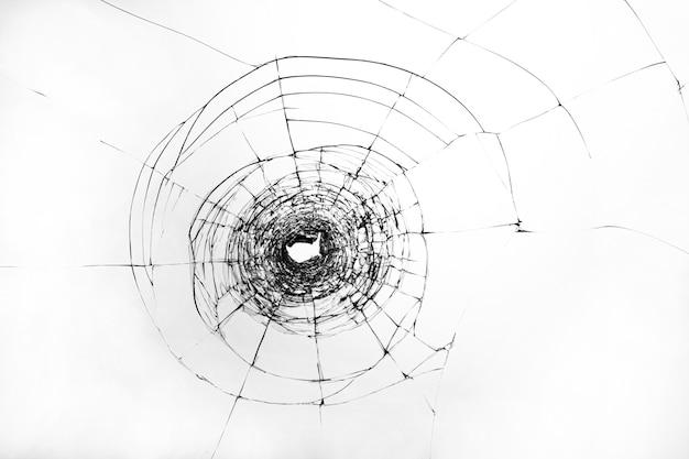 Rachaduras em vidro quebrado. a janela é danificada por um tiro de arma de fogo. pára-brisa transparente de um carro com um furo após os disparos.