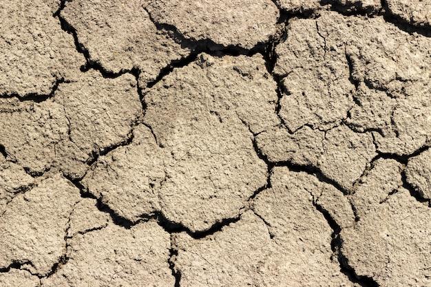 Rachaduras no chão em fundo de dia ensolarado