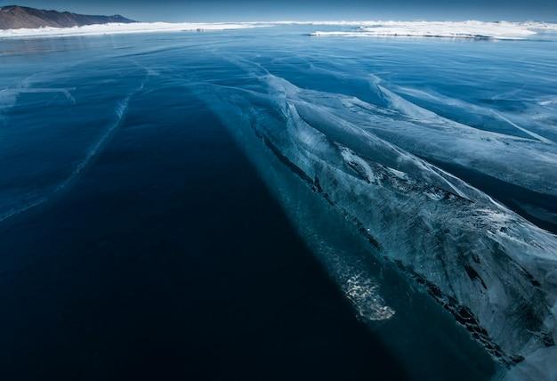 Rachaduras no gelo de um lago de inverno no inverno com tempo ensolarado