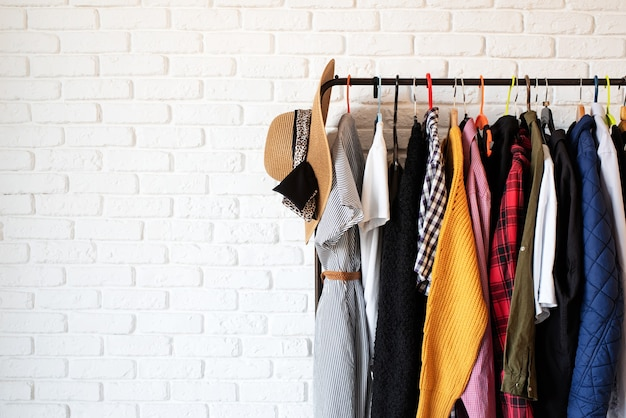 Rack com roupas coloridas em cabides sobre fundo de parede de tijolo branco com espaço de cópia