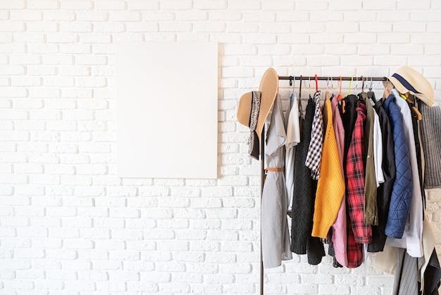 Rack com roupas coloridas em cabides sobre parede de tijolos brancos