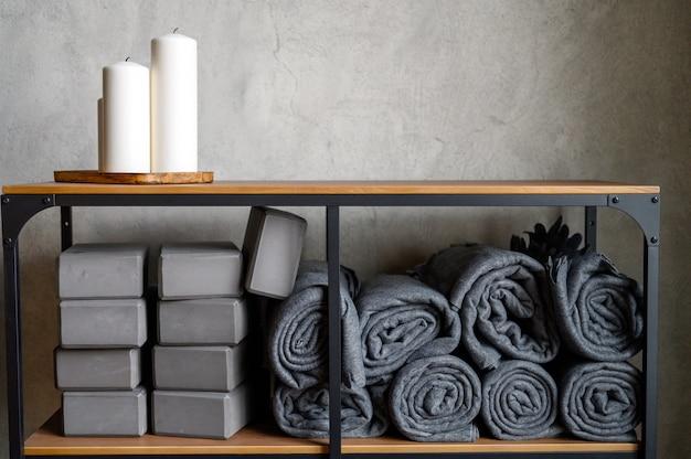 Rack de mesa com velas decorativas e acessórios para aulas de ioga.
