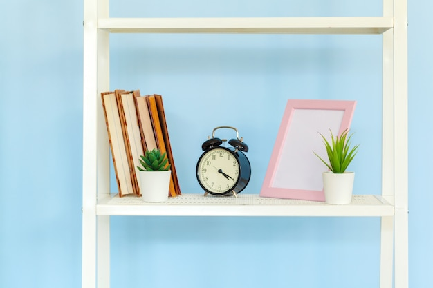 Rack de metal branco com livros contra a parede azul