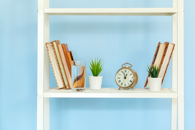 Rack de metal branco com livros contra a superfície azul