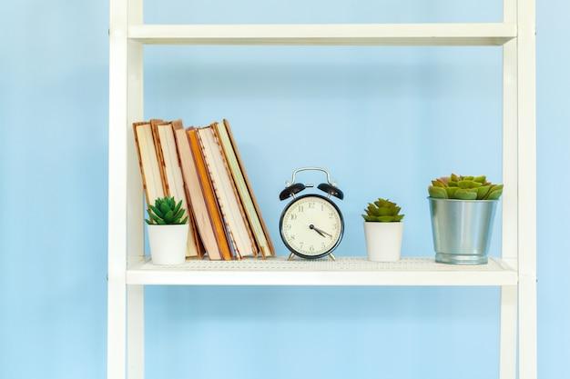 Rack de metal branco com livros contra o fundo azul