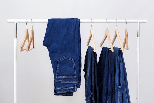 Rack de metal com cabides de madeira e jeans azul