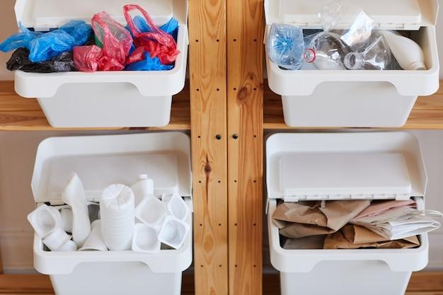 Rack de prateleiras de madeira com quatro recipientes de plástico para coleta seletiva em casa, preparado para a reciclagem