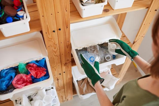 Rack de prateleiras de madeira com recipientes de plástico para coleta seletiva em casa, armazenamento e conceito de reciclagem