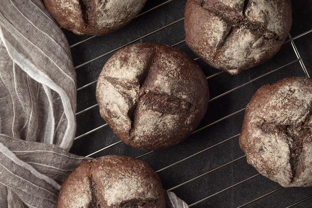 Rack de refrigeração com pães caseiros frescos de centeio em fundo cinza, vista superior