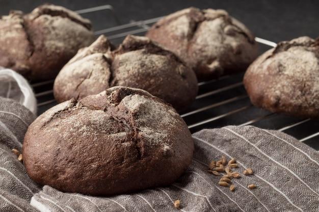 Rack de refrigeração com pão de centeio fresco sobre fundo cinzento, closeup
