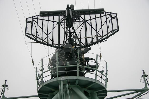 Radar em um navio de guerra com plataforma circular para pessoas. muitos fios e peças. tempo chuvoso e sombrio.