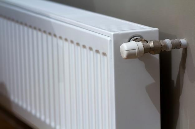 Radiador de aquecimento branco com válvula termostato na parede no interior de um apartamento após obras de renovação.