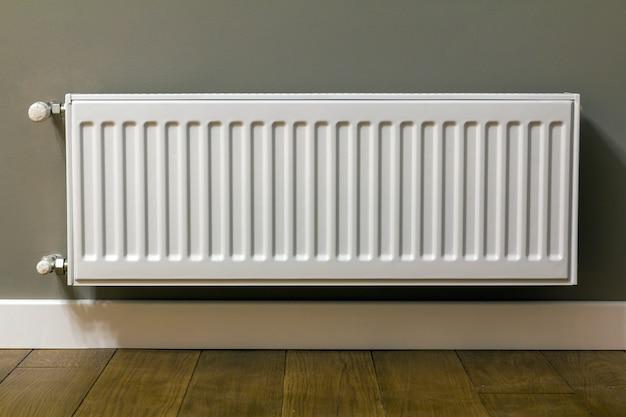 Radiador de aquecimento branco na parede de um apartamento com piso de madeira