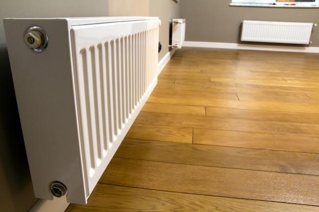 Radiador de aquecimento de metal branco montado em parede cinza dentro de uma sala.