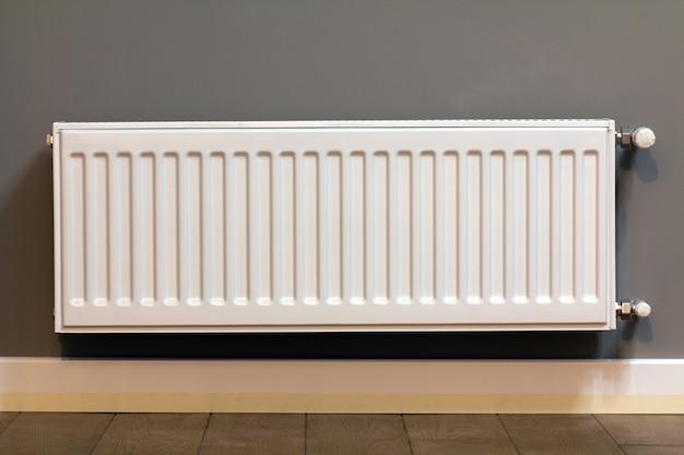Radiador de aquecimento de metal branco montado na parede cinza dentro de uma sala.