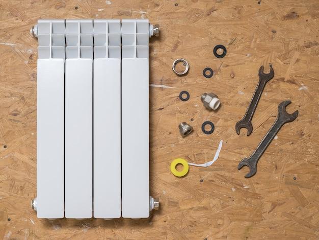 Radiador de quatro seções e uma ferramenta para reparo de abastecimento de água e sistemas de aquecimento. acidente do sistema de aquecimento de uma casa privada. radiador de aquecimento.