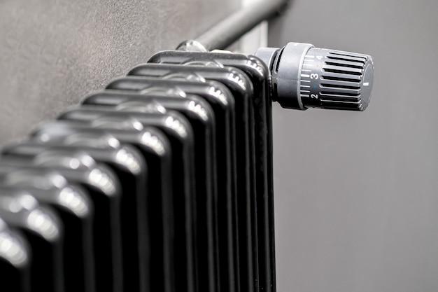 Radiador preto, aquecedor ambiente com controlador de temperatura.